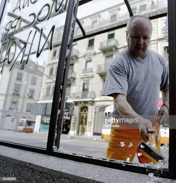 Swiss worker cleans up broken glass from a bus shelter June 2 2003 in Geneva Switzerland Thousands of anticapitalist protestors created havoc in...
