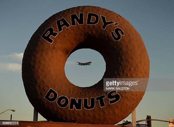 A Swissair plane flies past Randy's Donuts which is an iconic landmark in the city of Inglewood as it makes its descent into Los Angeles...