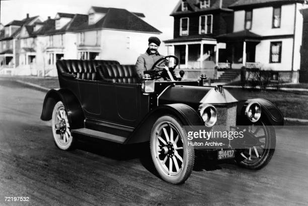 Swissborn automobile designer and racing driver and Louis Chevrolet sits behind the wheel of his prototype car 1911 The car went into production as...