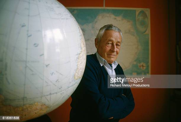 Swiss-born French polar explorer Paul-Emile Victor stands next to a large globe at home.