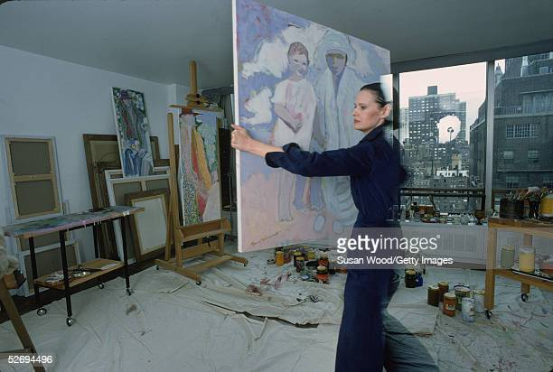 Swissborn socialite Gloria Vanderbilt carries a painting in her studio at her home in the UN Towers New York New York March 1976