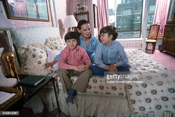 Swiss-born socialite Gloria Vanderbilt poses with her two sons Anderson Cooper and Carter Vanderbilt Cooper on her bed in their apartment in the UN...