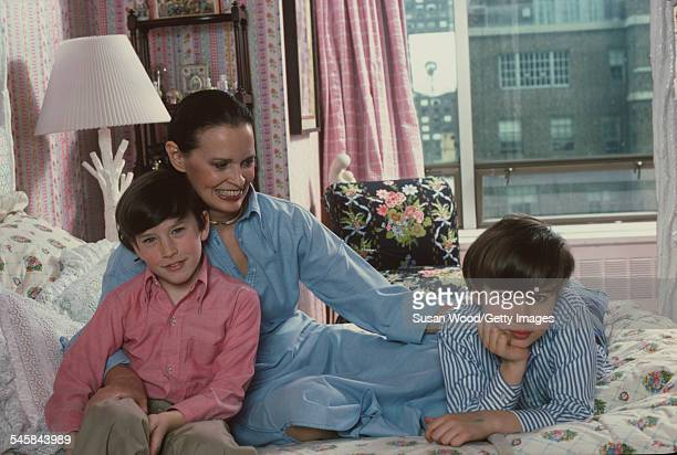 Swissborn socialite Gloria Vanderbilt poses with her two sons Anderson Cooper and Carter Vanderbilt Cooper on her bed in their apartment in the UN...