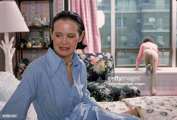 Swissborn socialite Gloria Vanderbilt sits on the bed in her apartment in UN Towers New York New York March 1976 Her son Anderson Cooper kneels while...