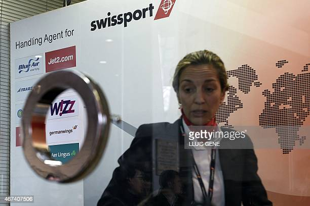 A Swissport employee stands inside a booth in terminal 2B at Barcelona's El Prat airport on March 24 2015 after a Germanwings airliner crashed near a...