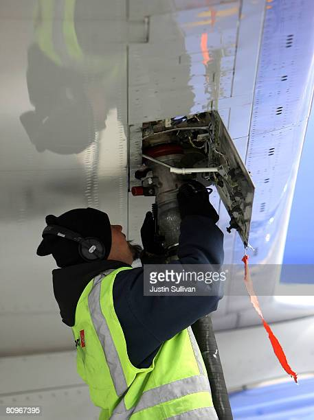 Swissport employee Steve Surla monitors a fueling hose as he pumps fuel into a Southwest Airlines plane May 2 2008 at Oakland International Airport...