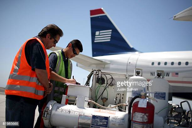 Swissport employees Jim Stucky and Vaudillo Nievies check a fuel log after refueling a US Airways plane at the Oakland International Airport July 18...