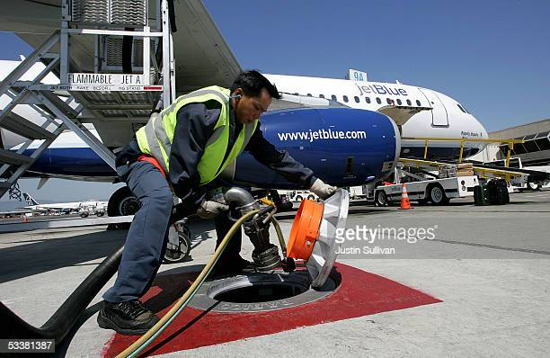Swissport fueler Benedicto Perez unplugs a fuel line from a ground tank after filling a JetBlue plane at the Oakland International Airport August 12...