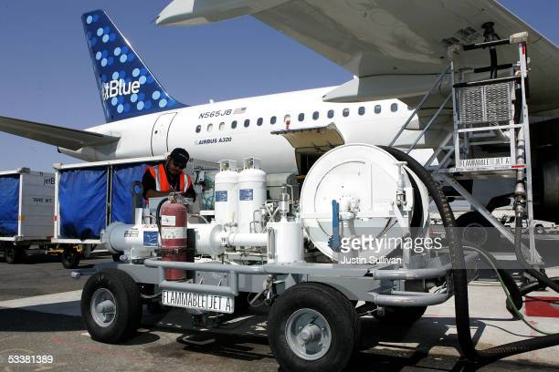 Swissport fueler Frances Santos calculates the amount of fuel being used while filling a JetBlue plane at the Oakland International Airport August 12...