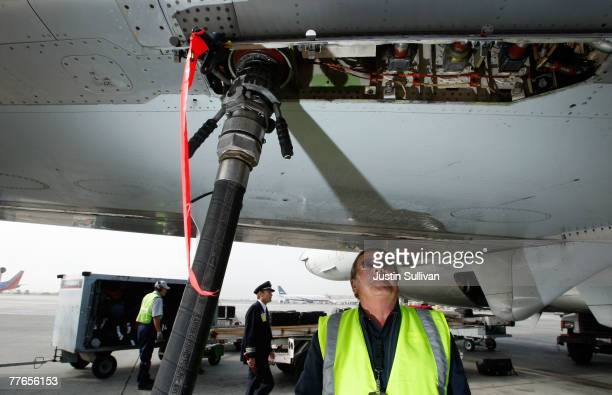 Swissport fueler Miroslaw Szymczak monitors a fueling hose while refueling an American Airlines plane November 2 2007 at the Oakland International...