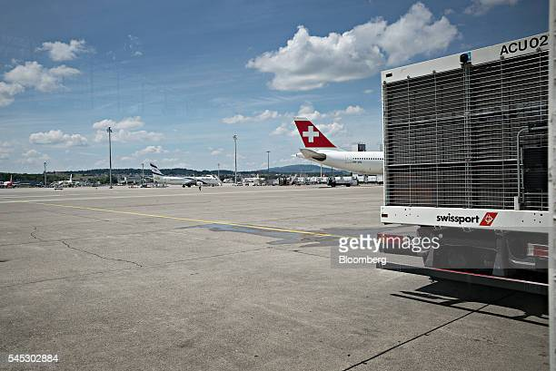 A Swissport International Ltd branded truck sits parked as a passenger aircraft operated by Swiss International Air Lines AG stands beyond at Zurich...