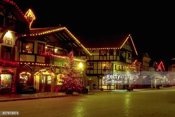 Swissstyle buildings which look like chalets are lit up with colored lights at Christmastime in Leavenworth Washington
