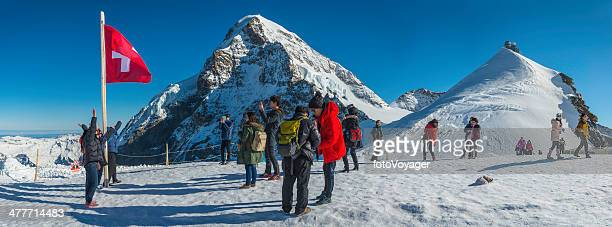 Switzerland Alps Japanese tourists enjoying winter mountain sunshine Sphinx Jungfraujoch