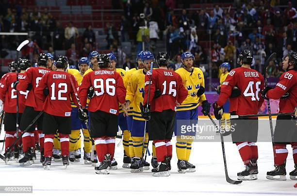 Switzerland and Sweden shake hands after their Men's Ice Hockey Preliminary Round Group C game on day seven of the Sochi 2014 Winter Olympics at...
