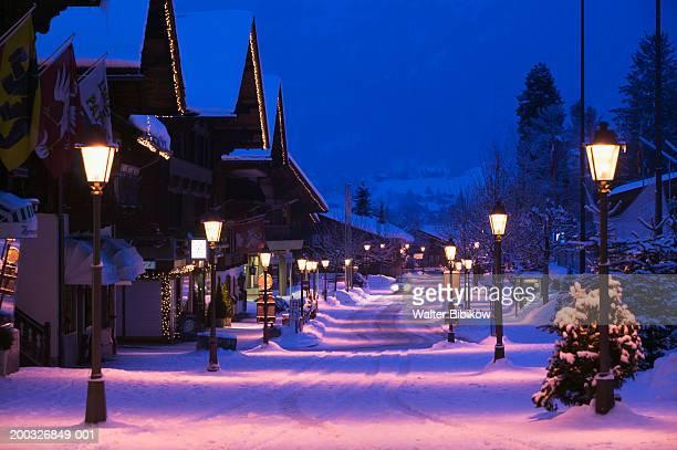 switzerland, bern, gstaad, saanenstrasse, street scene, winter, dawn - gstaad stock pictures, royalty-free photos & images