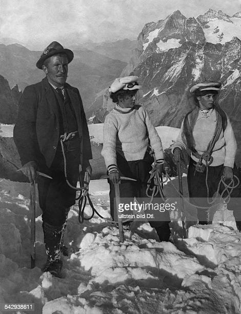 Switzerland BernKanton Alpine climbing On the summit a man and two women ascent the Jungfrau The Jungfrau is one of the main summits in the Bernese...