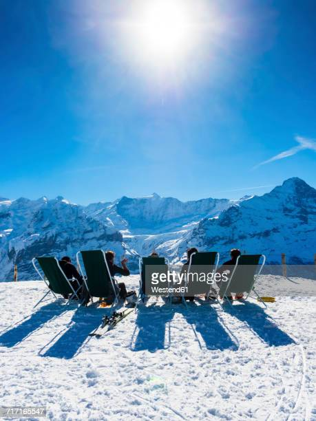 Switzerland, Canton of Bern, Grindelwald, view from First to Wetterhorn and Eiger, skiers sitting on deckchairs in the sun