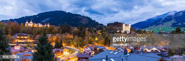 switzerland, canton of bern, gstaad, townscape with gstaad palace hotel at dusk - グスタード ストックフォトと画像