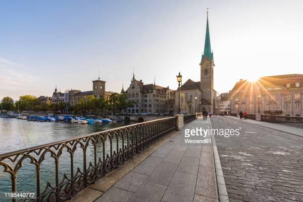switzerland, canton of zurich, zurich,†munsterbrucke†bridge at sunset with†fraumunster†church in background - zurich stock pictures, royalty-free photos & images