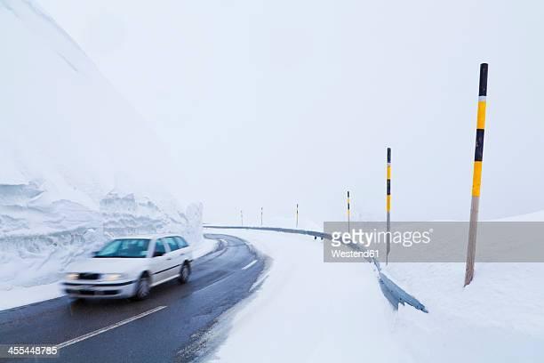 Switzerland, Car passing through snow covered road