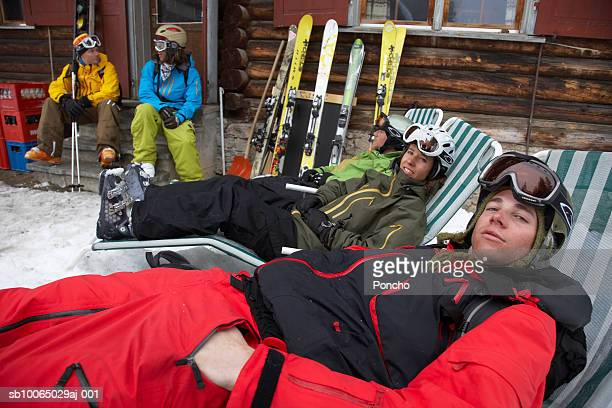 switzerland, davos, group of skiers resting outside cabin - apres ski stock pictures, royalty-free photos & images