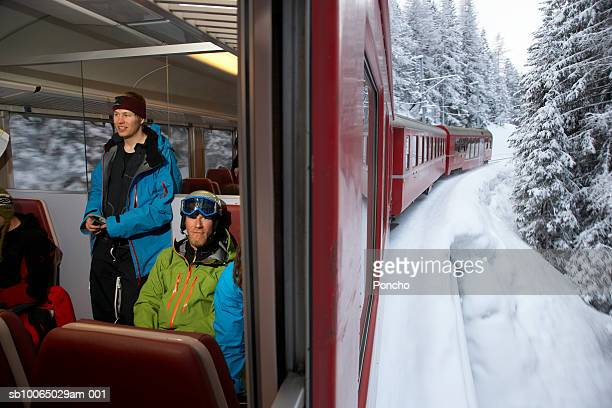switzerland, davos, skiers sitting in train - davos stock-fotos und bilder