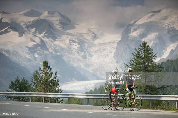 switzerland, engadin, two cyclists on bernina pass road in front of morteratsch glacier - mountain pass stock pictures, royalty-free photos & images