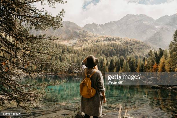 switzerland, engadin, woman on a hiking trip standing at lakeside in mountainscape - außergewöhnlich stock-fotos und bilder