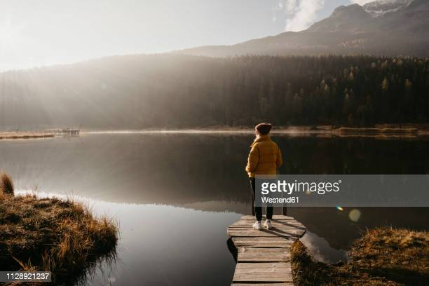 switzerland, engadine, lake staz, woman standing on a jetty at lakeside in morning sun - morgen stock-fotos und bilder