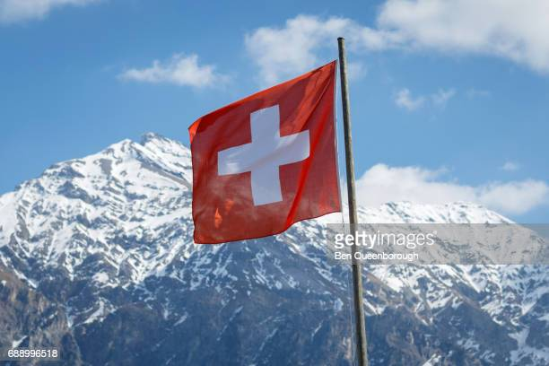 Switzerland flag in front of a Mountain Landscape