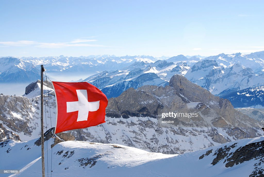 switzerland flagg over swiss alps : Stock Photo