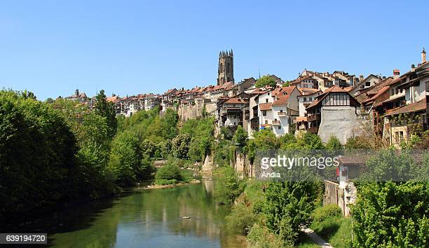Fribourg. The Saane or Sarine river, the historic centre and the steeple of the Cathedral of St. Nicholas .