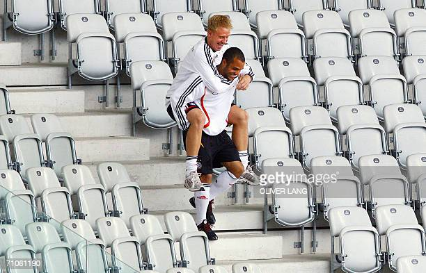 Germany's midfielder David Odonkor carries striker Mike Hanke on his shoulders prior a training session of the national football team at the Stade de...