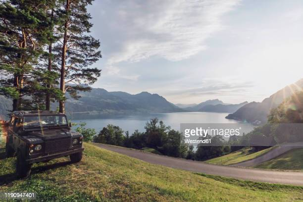 switzerland, gersau, schwyz, 4x4 car parked along winding road with lake lucerne in background - schwyz stock pictures, royalty-free photos & images