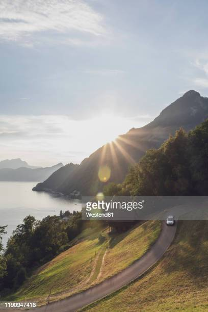 switzerland, gersau, schwyz, car driving along winding road at sunset with lakelucernein background - schwyz stock pictures, royalty-free photos & images
