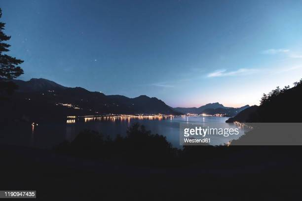 switzerland, gersau, schwyz, illuminated houses along coastline of lake lucerne at dusk - schwyz stock pictures, royalty-free photos & images