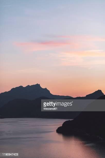 switzerland, gersau, schwyz, silhouettes of hills surrounding lake lucerne at summer dusk - schwyz stock pictures, royalty-free photos & images