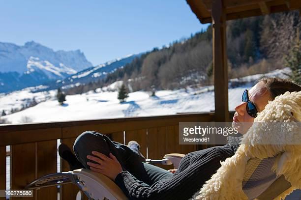switzerland, graubuenden, savognin, woman relaxing on sun terrace - apres ski stock pictures, royalty-free photos & images