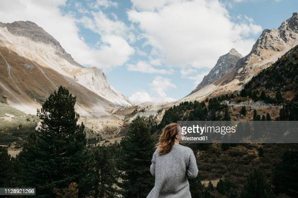 switzerland, grisons, albula pass, woman standing in mountainscape - swiss alps stock pictures, royalty-free photos & images
