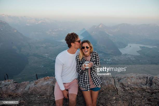 switzerland, grosser mythen, happy young couple on a hiking trip having a break at sunrise - hot love stock pictures, royalty-free photos & images