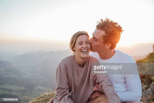 switzerland, grosser mythen, happy young couple on a hiking trip having a break at sunrise - schwyz stock pictures, royalty-free photos & images