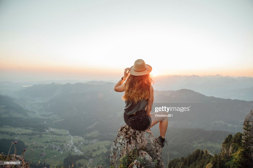 Switzerland, Grosser Mythen, young woman on a hiking trip sitting on a rock at sunrise : Stock-Foto