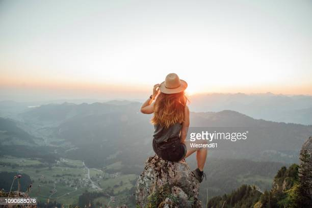 switzerland, grosser mythen, young woman on a hiking trip sitting on a rock at sunrise - turista foto e immagini stock