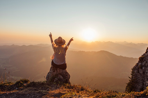 Switzerland, Grosser Mythen, young woman on a hiking trip sitting on a rock at sunrise - gettyimageskorea