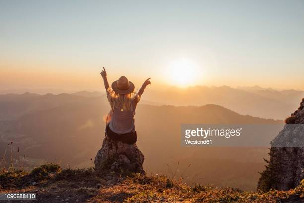 switzerland, grosser mythen, young woman on a hiking trip sitting on a rock at sunrise - gegenlicht stock-fotos und bilder