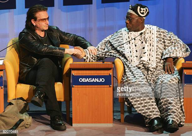 Irish singer Bono congratulates Nigerian President Olusegun Obasanjo after the President addressed the session 'The G8 and Africa Rhetoric or action...