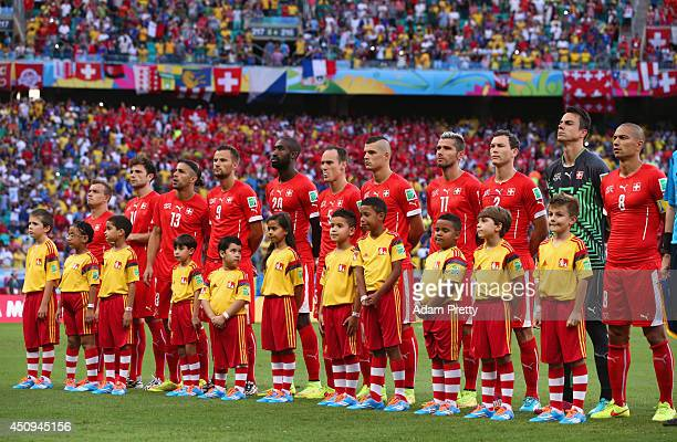 Switzerland line up with their player escorts for the National Anthems prior to the 2014 FIFA World Cup Brazil Group E match between Switzerland and...
