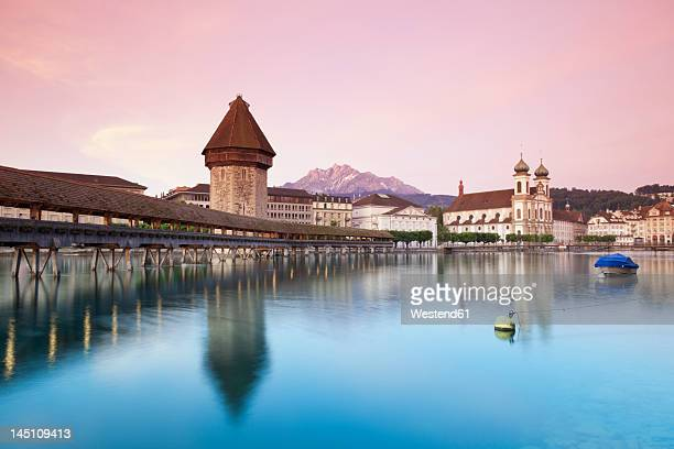 Switzerland, Lucerne, View of water tower, bridge and church in morning
