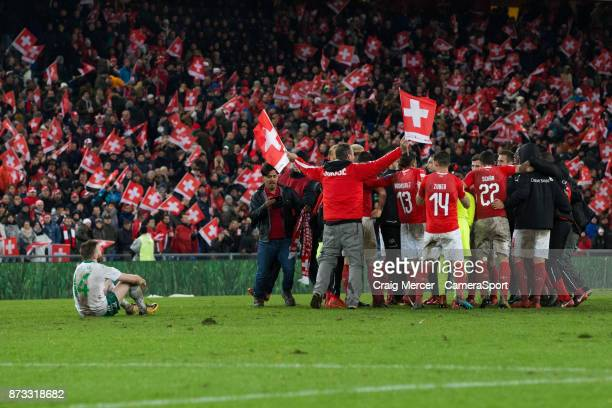 Switzerland players celebrate as Northern Ireland's Stuart Dallas sits dejected after the FIFA 2018 World Cup Qualifier PlayOff Second Leg between...