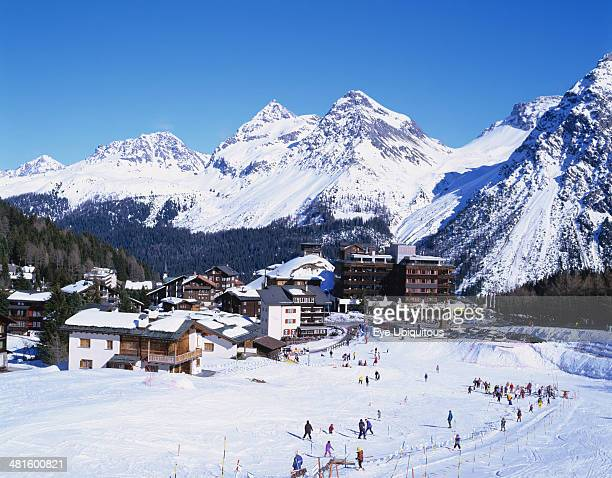 Switzerland, Plessur, Arosa, Ski resort with people skiing in the foreground and the Alps behind.